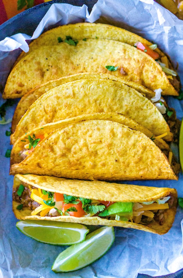 4 tacos on a plate with lime wedges.