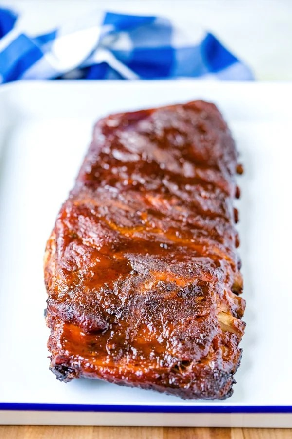 Smoked spare ribs rack on a white platter after it's fully cooker.