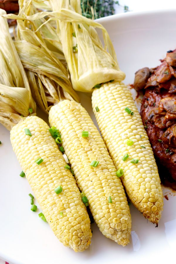 Buttery smoked corn on the cob on a white plate with a grilled steak.