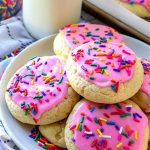 Round sugar cookie with pink frosting and rainbow sprinkles.