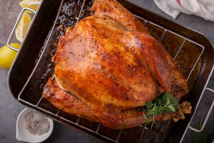 A finished roast turkey in a roasting pan.