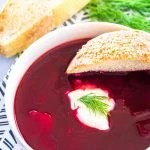 A bowl of Polish Beet Soup with a side of bread
