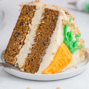 A close up picture of a slice of Cheesecake Factory Carrot Cake Copycat on a white plate.