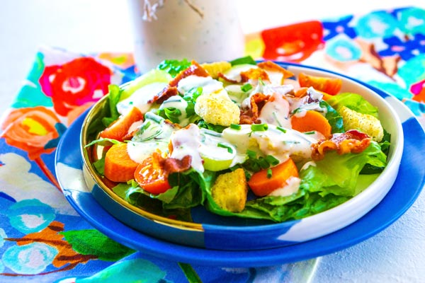 Salad on a plate that is drizzled with homemade ranch dressing.