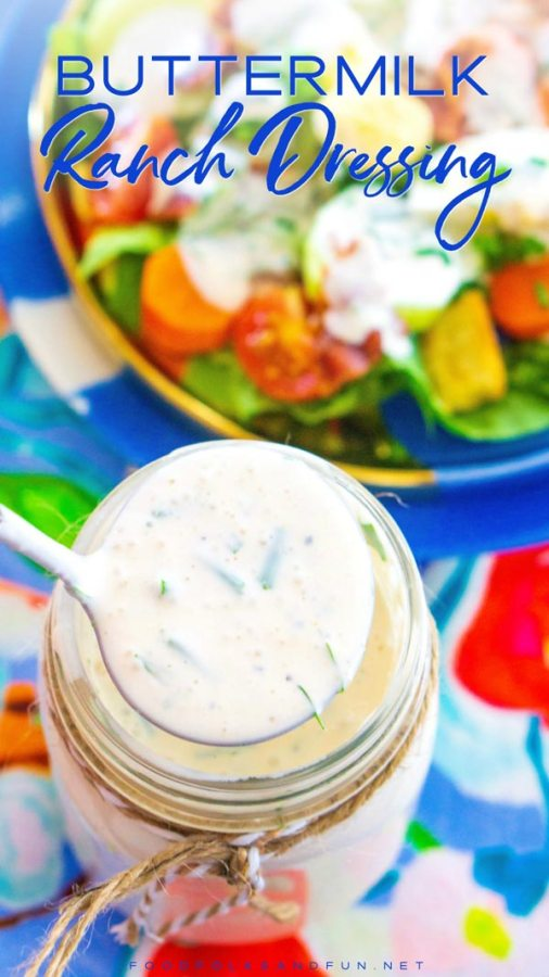 Ranch dressing in a Mason jar being ladled over a salad.