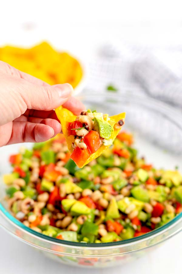 A chip being dipped into the cowboy caviar recipe.
