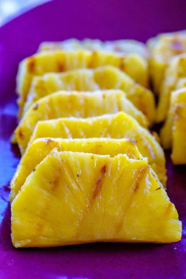 Grilled pineapple with grill marks on a serving platter.