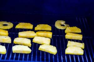 Sliced pineapple cooking on the grill.
