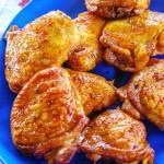 Teriyaki chicken on a blue platter.