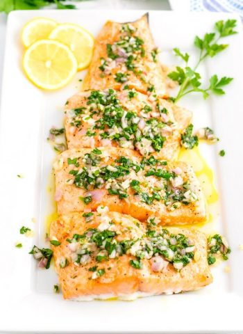 Cooked salmon on a white serving platter.