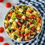 Italian dressing pasta salad in a white bowl with cherry tomatoes around it.