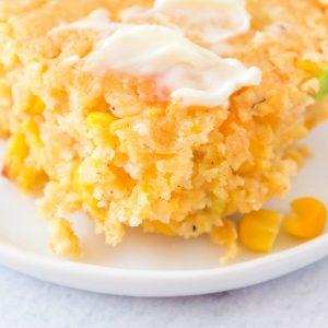some cornbread casserole on a white plate.