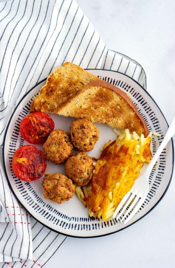 Sausage and cheese balls served for breakfast with a plate of toast, hash browns, and cooked tomato halves.