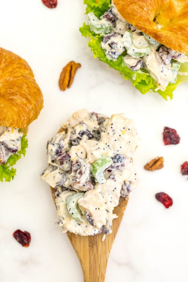 A spoonful of chicken salad with 2 sandwiches in the background.