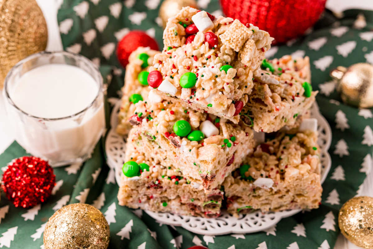 Easy Christmas Treats stacked on top of each other on a white plate with a glass of milk nearby.