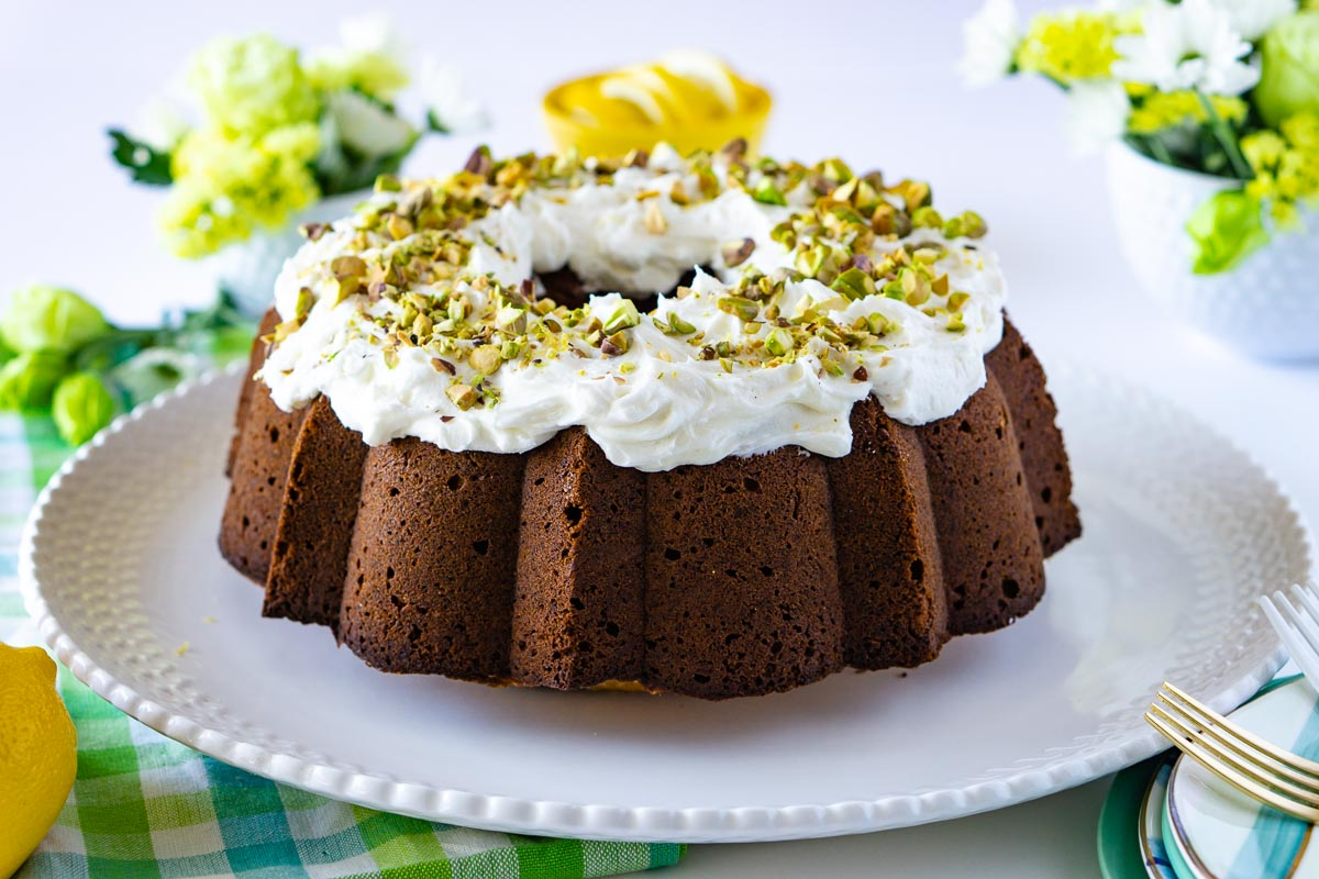 The entire Pistachio Bundt Cake on a white cake plate. It has lemon frosting on top and chopped pistachios .