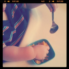 baby hands eating macaroni