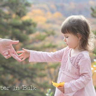 little girl reaching for her dad's hand