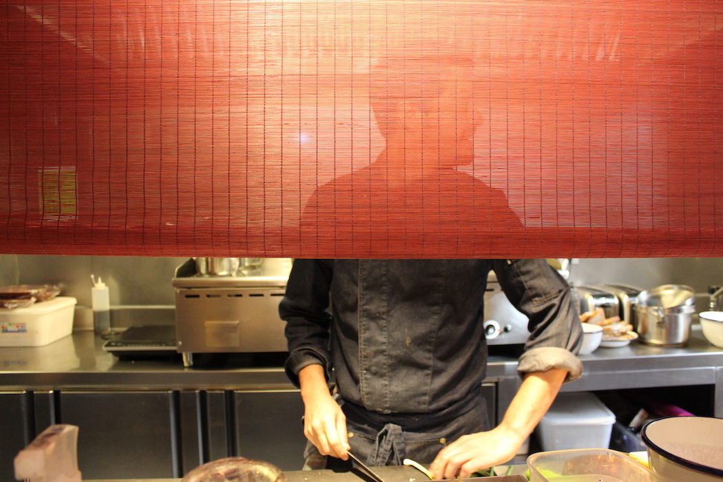 The blind separating the hot kitchen from the dining area at Pepa Pla