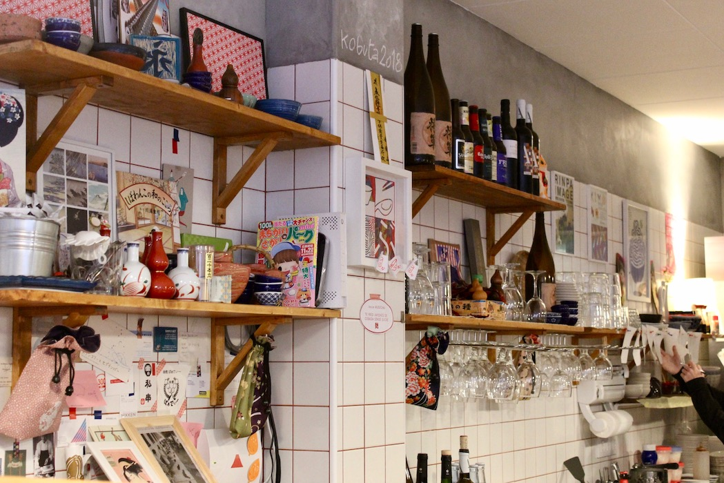 The space behind the bar at Kobuta Ramen filled with Japanese prints stuck to the white tiles with washi tape.