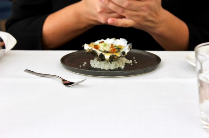 A single oyster, sitting on crushed salt on a black plate, white tablecloth with the hands of a woman crossed as she uses her iPhone.