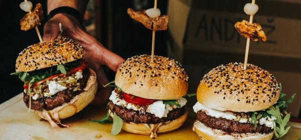 Une main dépose un troisième hamburger sur une planche en contenant déjà deux.