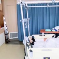38岁应采儿双腿打石膏,半卧病床进行康复训练,病房内追看奥运会