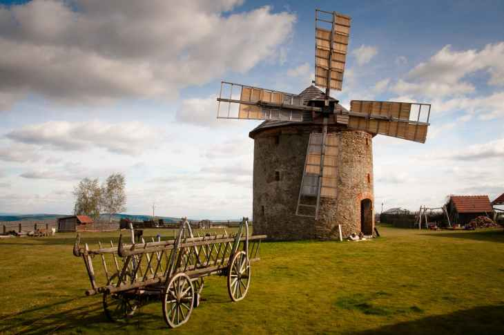 wooden windmill near wooden carriage during daytime