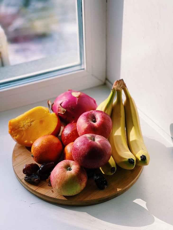 plate of fresh assorted fruit on windowsill