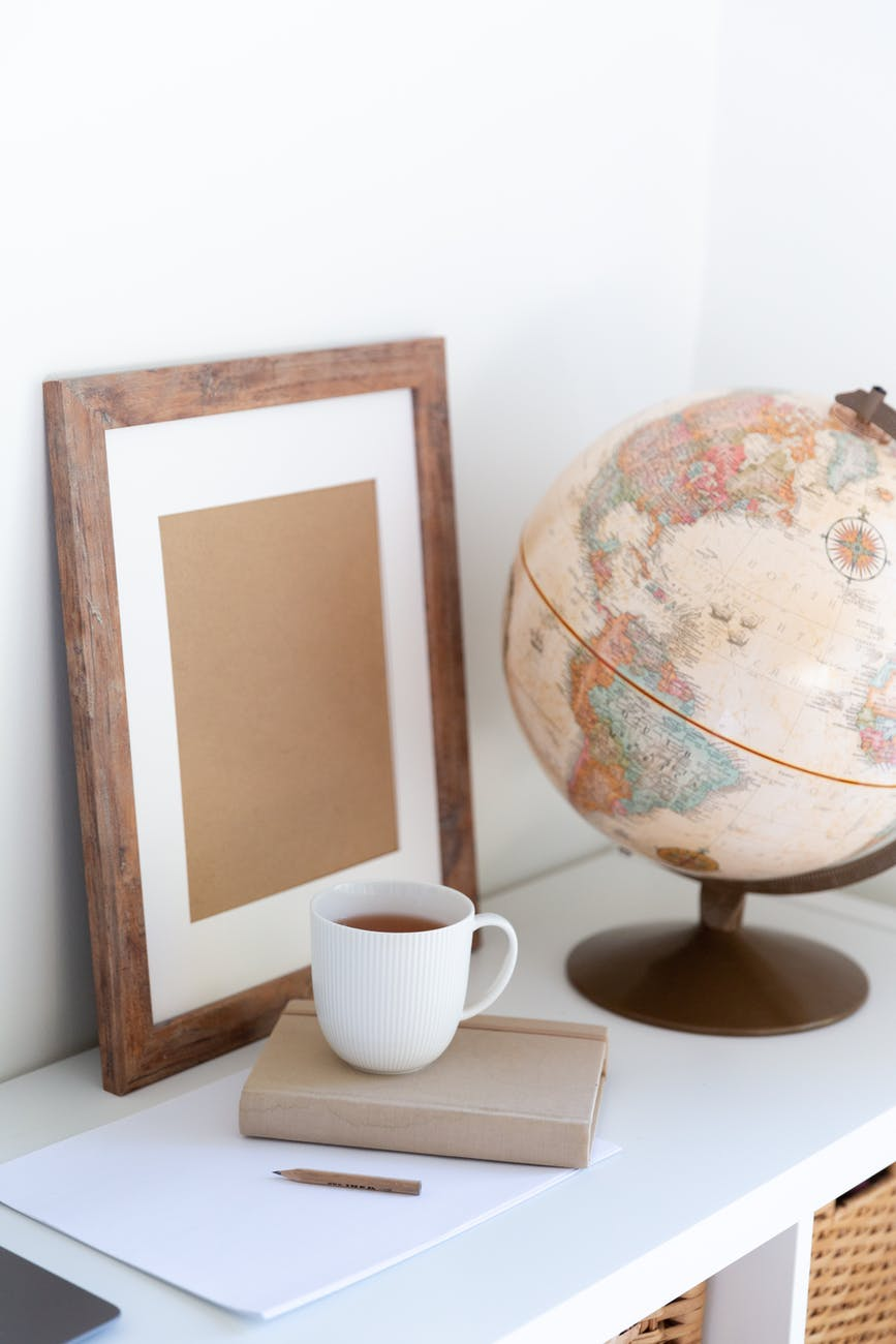 vintage globe near blank frame and cup of tea placed on book in office