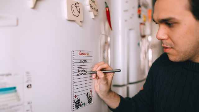 young man writing reminder on fridge note