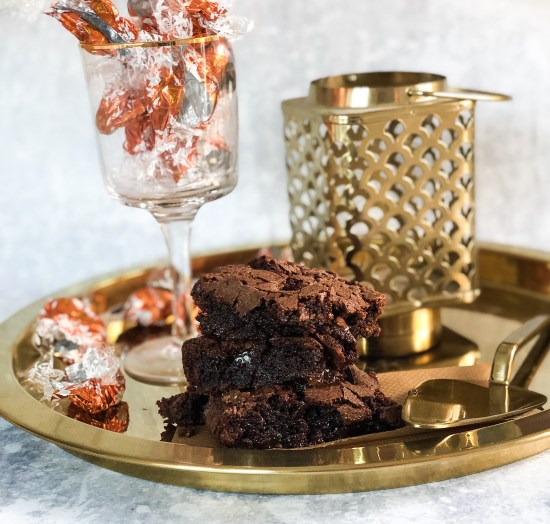 Stack of Chocolate Orange Brownies on a Gold Platter and Lantern