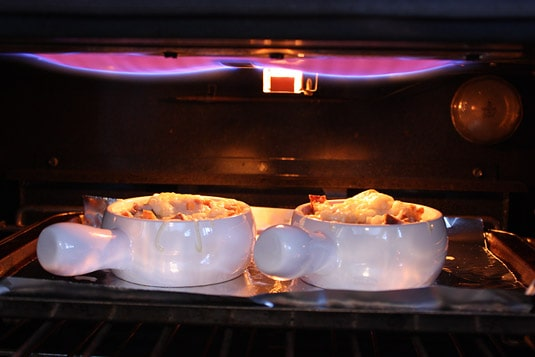 Two French onion soups under the broiler.