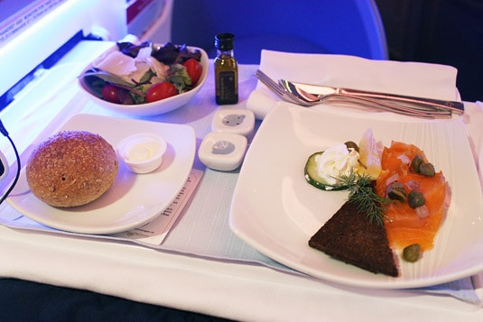 First Class Appetizer and Salad: Smoked Salmon with Cream Cheese, Capers, Onions, Cucumbers, Caper Berries and Pumpernickel Bread; Field Greens, Grape Tomatoes, Shaved Parmesan and Balsamic Vinaigrette