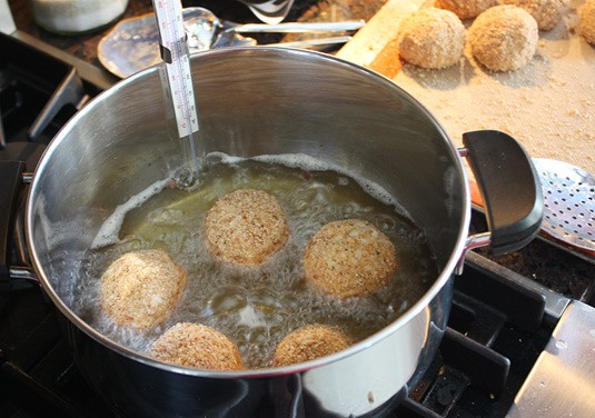 Making Arancine con Ragù: To fry the rice balls: When the oil comes to temperature, carefully slip 4 or 5 rice balls into the oil (don't overcrowd the pot). Fry, turning as necessary with tongs or a slotted spoon, until golden brown and crisp on all sides, about 4 minutes.
