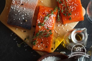 Salmon filets served on wooden cutting board