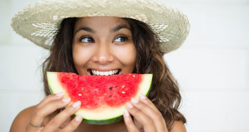 woman with straw hat holding watermelon slice to mouth