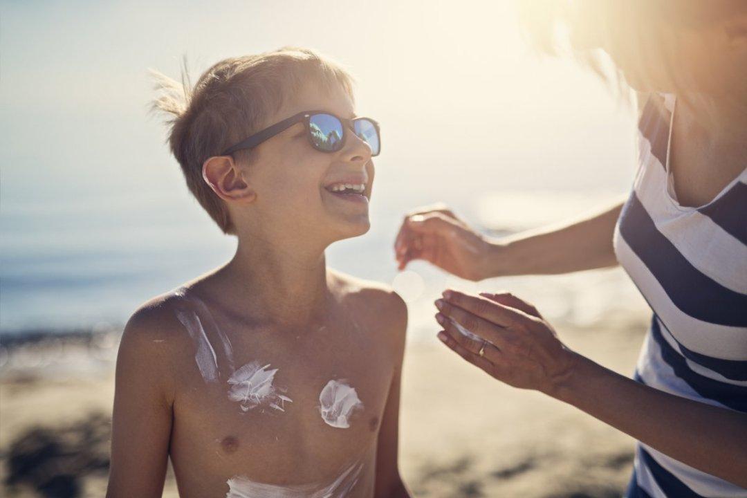 母親在海灘上把防曬霜放在她的太陽