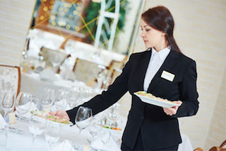 Female catering staff member wearing suit working at an event at an upscale venue. She is setting food presented on fine china on a table.