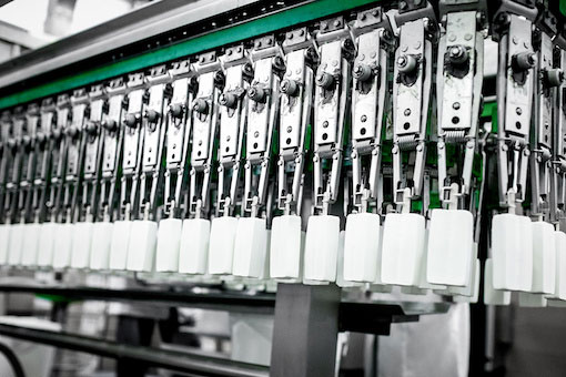 White popsicles hanging from manufacturing machinery