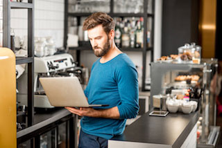 Restaurant manager dressed in jeans and long sleeve shirt holding a laptop and glancing at the screen from behind the cafe counter