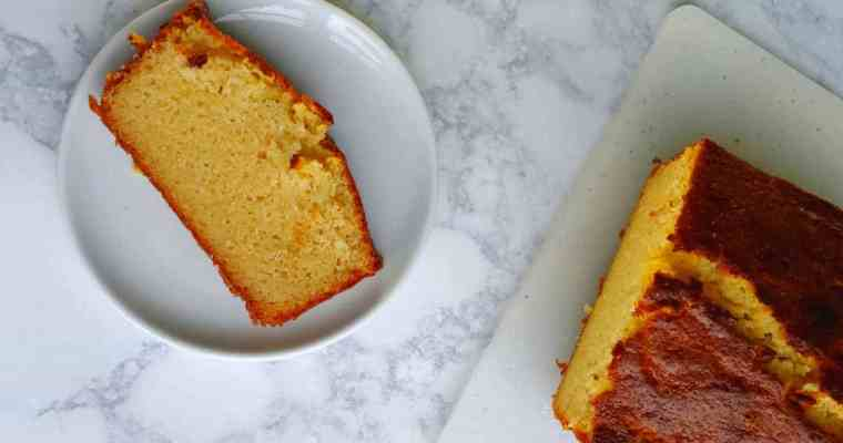 a slice of ricotta pound cake beside the loaf