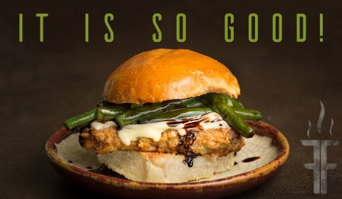 The sandwich is chicken fried steak, green beans coated in balsamic glaze, fresh mozzarella, green onions on a hamburger bun.