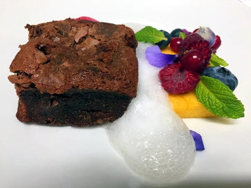 Brownie con esponja de maracuyá, sorbete frambuesa y aire de cava