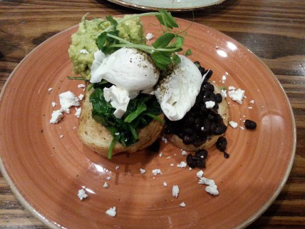 Issus Cafe Bar. Avocado smash with refried black beans, poached egg, feta and spinach on toasted sourdough