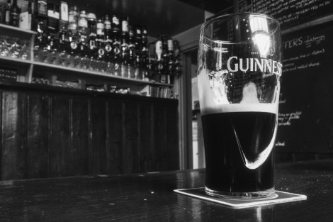 black and white photo of pint of guinness on bar