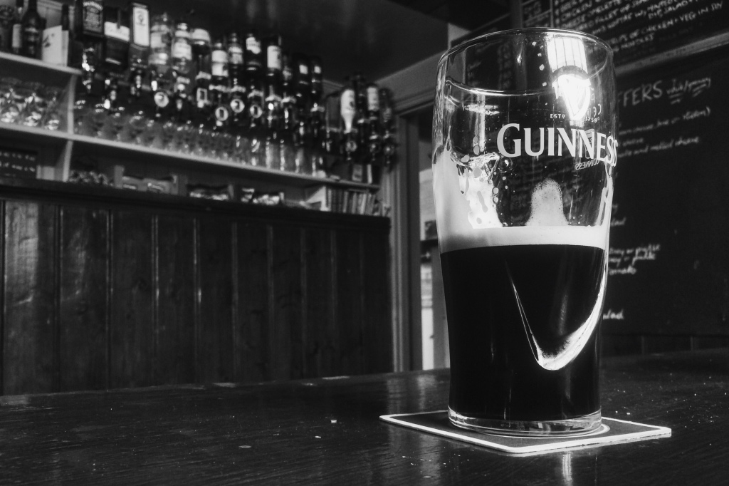 Black and white photo of pint of Guinness in a bar | Discovering Guinness on foodwithaview.com