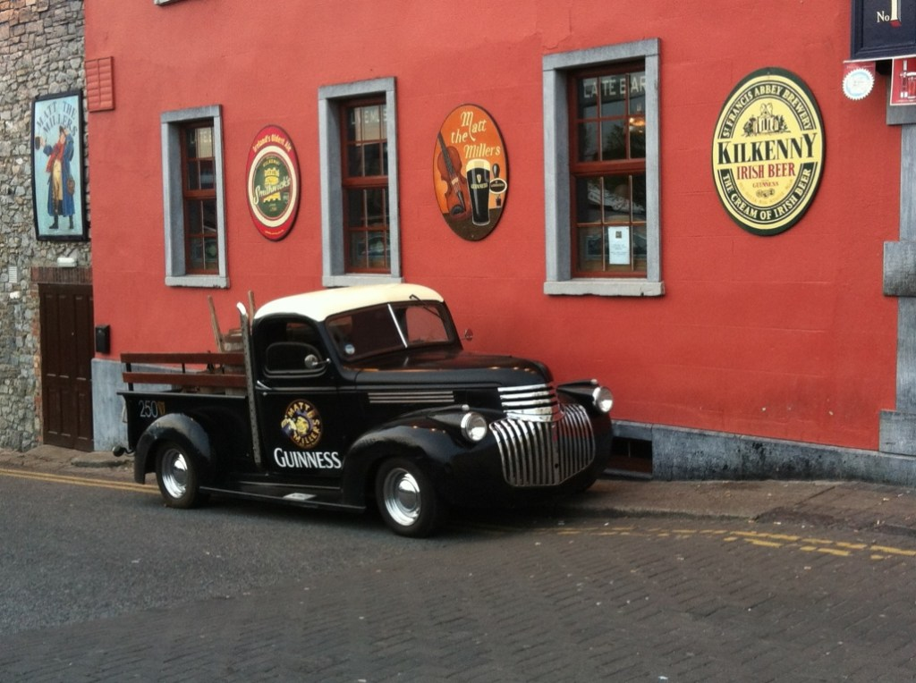 black guinness truck parked in front of red painted kilkenny ireland pub