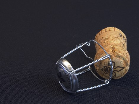champagne cork and wire on a black surface