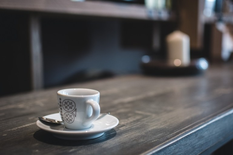 Coffee cup on a wooden table at a coffee shop | photo by foodiesfeed | Philadelphia restaurants on foodwithaview.com